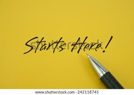 Starts Here! note with pen on yellow background
