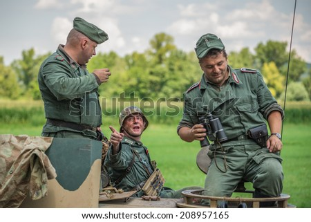 STARY TEKOV, SLOVAKIA - JULY 26,2014: German soldier talking to comrades on a tank during reenactment of World War II fight