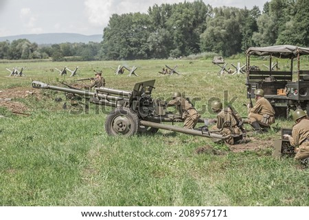STARY TEKOV, SLOVAKIA - JULY 26,2014:  Soviet soldiers using a cannon during reenactment of World War II fight - stock photo