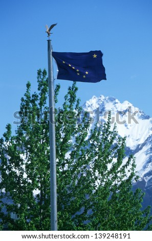 State Flag of Alaska with tree and mountain in the background