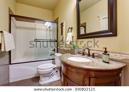 State of the art bathroom with glass shower and cream walls. - stock photo