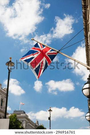 state sybols and national holidays concept - british nion jack flag waving on london city street - stock photo