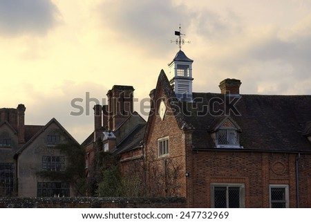 stately home with sunset clouds behind - stock photo