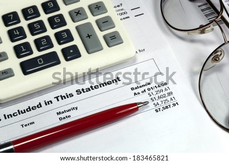 Statement of account, vintage pen, vintage calculator, vintage eye glasses, closeup desktop view.