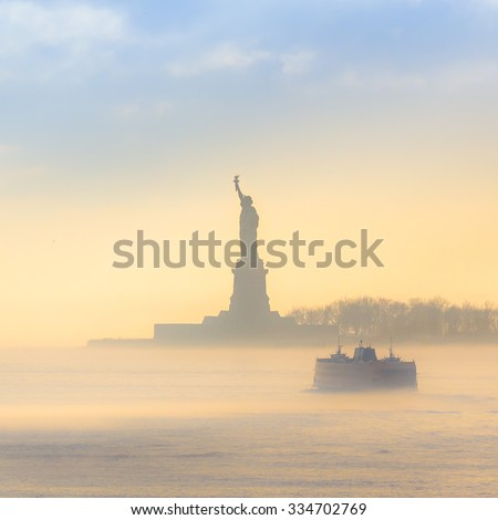 Staten Island Ferry cruises past the Statue of Liberty on a misty sunset. Manhattan, New York City, United States of America. Square composition. - stock photo