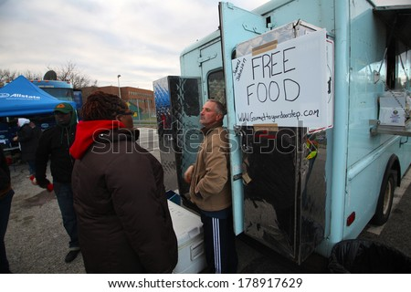 STATEN ISLAND, NEW YORK CITY - NOVEMBER 4 2012: Volunteers & national guard assembled at New Dorp High School to aid people recovering from Hurricane Sandy. Volunteer caterers offer free meals - stock photo