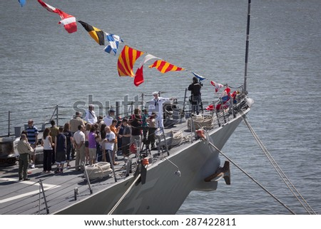 STATEN ISLAND, NY - MAY 24 2015: A US Navy sailor speaks to citizens during a public tour on the bow of guided-missile destroyer USS Stout (DDG 55) moored at Sullivans Pier during Fleet Week NY 2015.