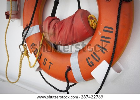 STATEN ISLAND, NY - MAY 24 2015: An orange lifering mounted to the wall of the USCGC Spencer (WMEC 905) a Medium endurance cutter at Sullivans Pier during Fleet Week NY 2015. - stock photo