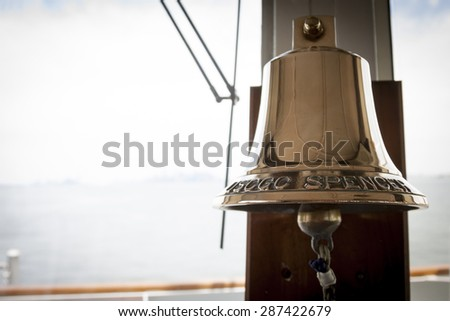 STATEN ISLAND, NY - MAY 24 2015: The brass bell  of the USCGC Spencer (WMEC 905) a Medium endurance cutter mounted by a window in the bridge at Sullivans Pier during Fleet Week NY 2015. - stock photo