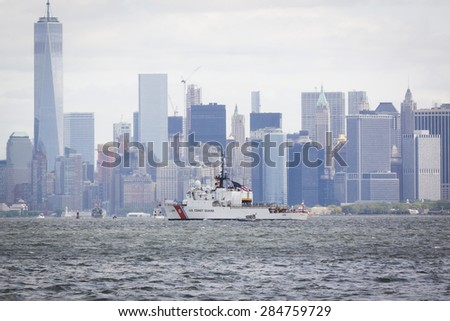 STATEN ISLAND, NY - MAY 20 2015: USCGC Spencer (WMEC 905) passes the Freedom Tower of One World Trade Center in Lower Manhattan on the Hudson River during the Parade of Ships which begins Fleet Week.  - stock photo