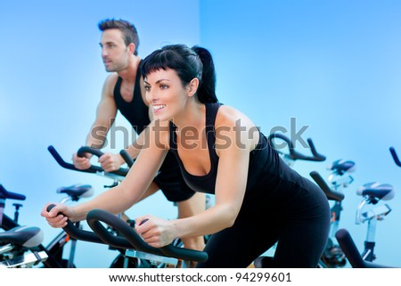 Stationary bicycles fitness girl in a gym sport club - stock photo