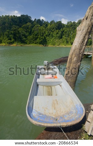 Stationary fishing boat on a calm lake. - stock photo