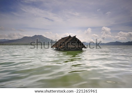 stationary water waves and Sunk house in lake batur   - stock photo