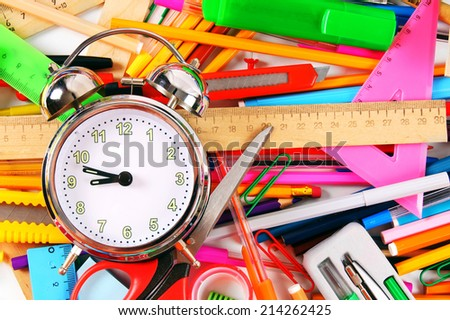 Stationery and alarm clock. A bright background.