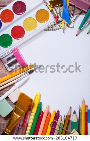 stationery and paint on wooden background