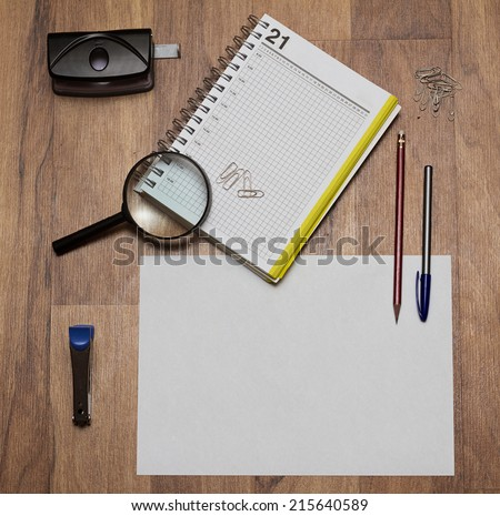 stationery consisting of notebook pen loop staples stapler and hole punch on the brown table - stock photo