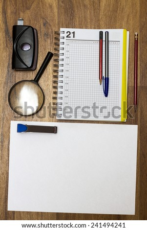 stationery consisting of notebook pen loop staples stapler and hole punch on the table - stock photo