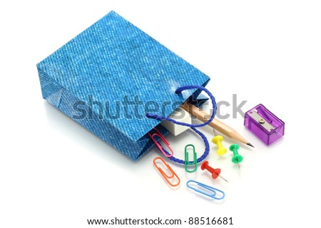 Stationery items poured out from shopping bag on white background - stock photo