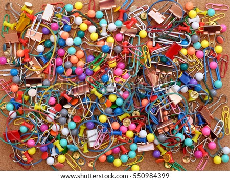 Stationery on cork background - colorful paper clips, rubber bands, push pins, treasury tags and binder clips