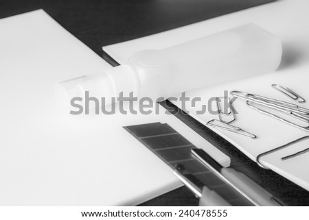 Stationery on the desk in the office, a knife on the paper with a clips