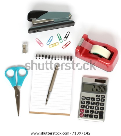 stationery supplies consisting of stapler scissors notebook pen calculator paper clips and pencil sharpener isolated on white background - stock photo