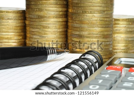 Stationery with stack of coins - stock photo