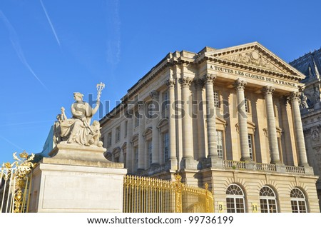 Statue and facade with columns of the Palace of Versailles, France