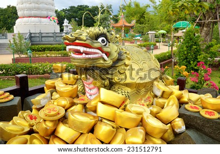 Statue and traditional chinese ancient gold bullion nugget. - stock photo