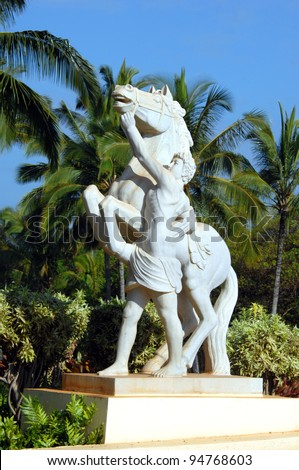 Statue depicts native hawaiian holding the bridle of an out of control horse.  Palm trees and statue are part of landscaping at resort on the island of Kauai, Hawaii. - stock photo