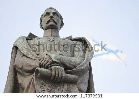 Statue in Kronstadt, St. Andrew's flag in the background, Russia - stock photo