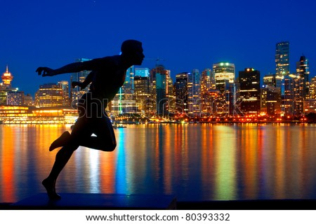 Statue in Stanley Park, Vancouver, British Columbia with a beautiful view of the city skyline behind. - stock photo