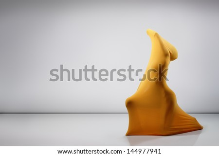 statue made of perfect sexy female body in yellow fabric posing at studio - stock photo