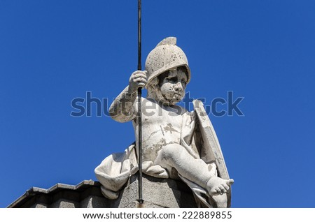 Statue of a boy on top of building in Spain - stock photo