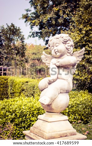 Statue of a child in garden vintage tone - stock photo