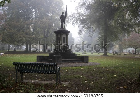 Statue of a Civil War soldier in a foggy graveyard - stock photo