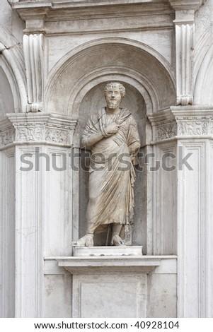 Statue of a man in a toga in an arched niche, Doges Palace, Venice - stock photo