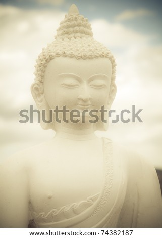 Statue of a white Buddha against clouds and sky - stock photo