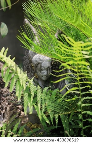 Statue of a woman hiding in the bushes.