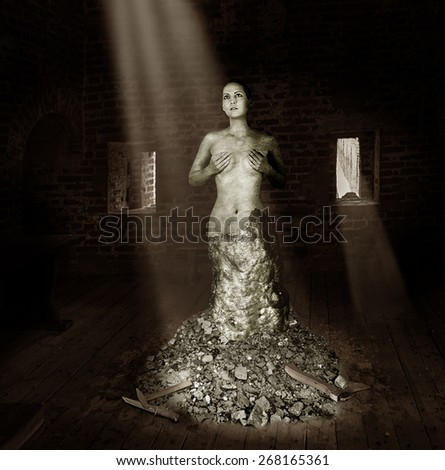 Statue of a woman made of stone stands in the old studio in the rays of light - stock photo