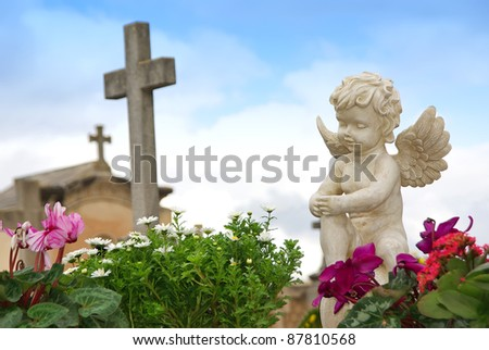 Statue of an angel boy located in a cemetery - stock photo
