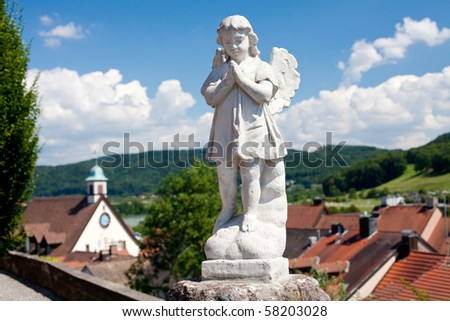 statue of angel over the town, trees and beautiful sky
