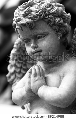 Statue of angel with folded hands praying - stock photo
