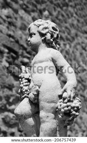 Statue of Bacchus (Dionysus) with grapes in his hands against rough stone wall. Garden sculpture. (Chateauneuf du Pape, Provence, France) Aged photo. Black and white. - stock photo