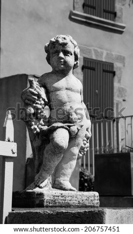 Statue of Bacchus (Dionysus) with grapes in his hands. Garden sculpture and old stone house with maroon wooden shutters at background. Chateauneuf du Pape, Provence, France Aged photo. Black and white - stock photo
