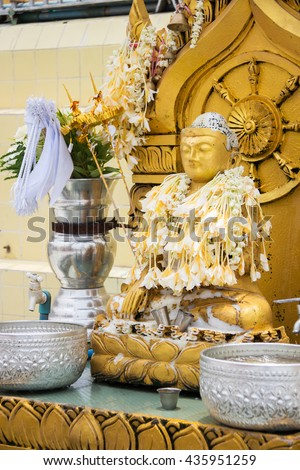 Statue of Buddha for offering of holy water at Botahtaung Pagoda in Yangon, Myanmar. - stock photo