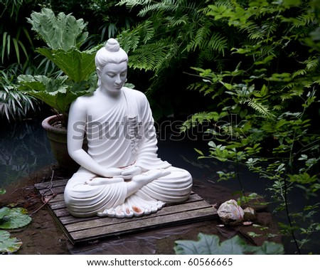 Statue of Buddha on wooden platform in pool surrounded by ferns - stock photo