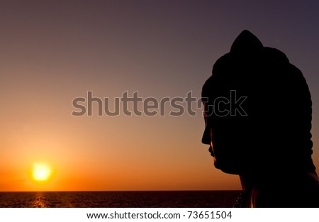 statue of buddha watching sunset over pacific ocean - stock photo