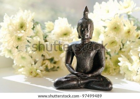 statue of Buddha with white flowers - stock photo