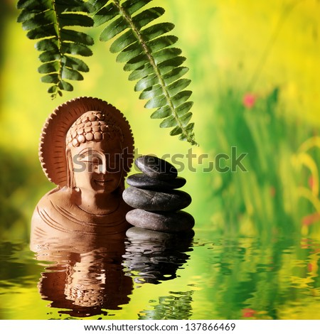 Statue of buddha with zen dark stones and leafs of fern on green brightful background, reflecting on water surface. - stock photo