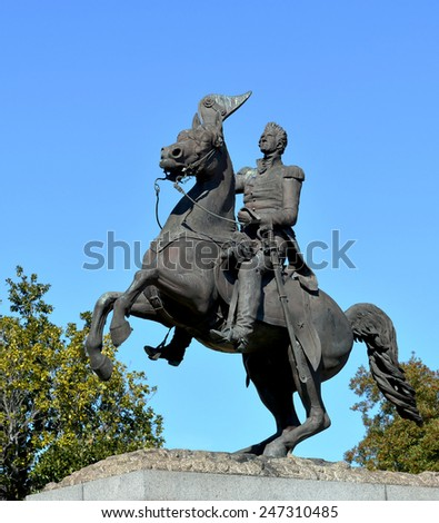 Statue of General Andrew Jackson on horseback against blue sky and trees. - stock photo